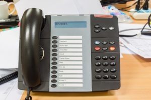 Black modern telephone on table in office